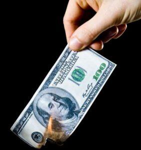 Hand holding a burning 100 dollar bill