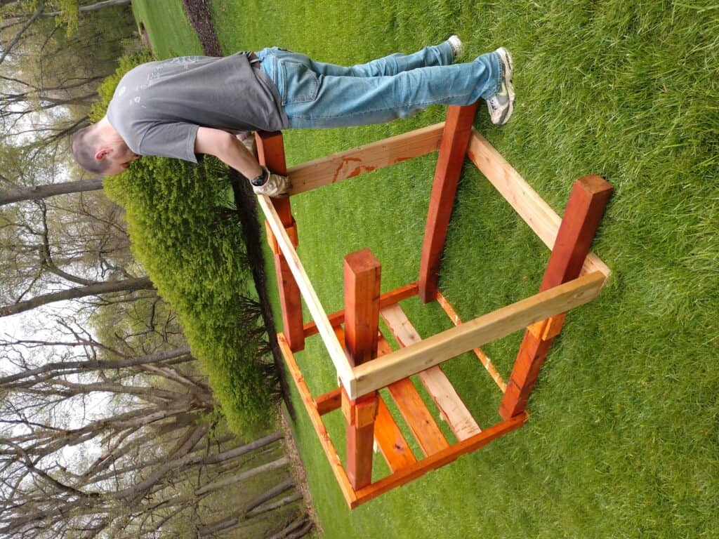 A man constructs a wooden structure that is lying on its side