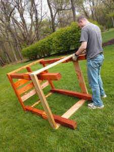 A man constructs a wooden structure that is lying on its side.